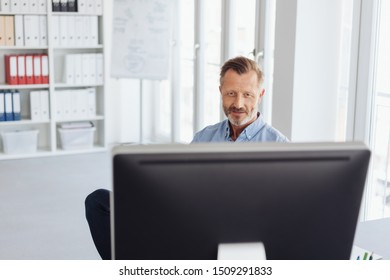 Businessman working behind a large desktop monitor viewed over the top in a large bright airy office