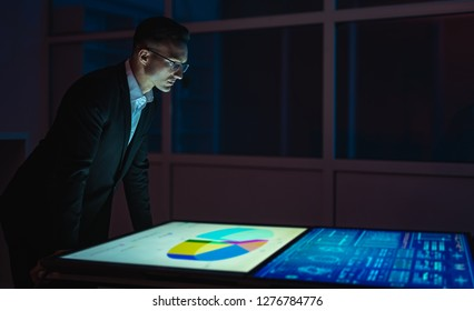 The businessman working with big screens in the dark room