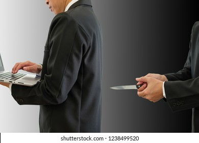 Businessman working in a bright place and a businessman secretly attacked in the dark. One man typing on keyboard computer and another man holding knife in back with clipping path.