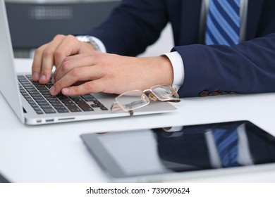 Businessman working by typing on laptop computer. Man's hands on notebook or business person at workplace. Employment  or start-up concept