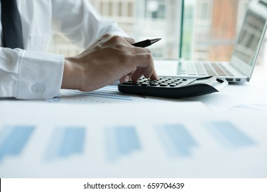 businessman working with calculator, business document and laptop computer notebook in office. male accountant doing accounting and calculating. bookkeeper making calculation. Savings, finance