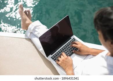 Geschäftsmann, der mit dem Computer auf dem Boot arbeitet, nettes Büro im Freien
