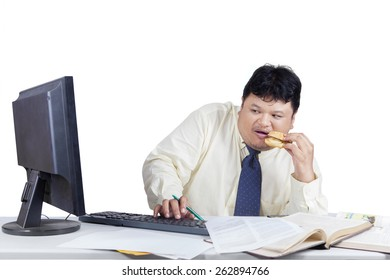 Businessman working with computer while eating burger and looks scared when looking the monitor