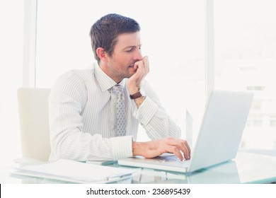 A businessman working at desk in his office