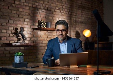 Businessman working at desk in loft office using smart phone.