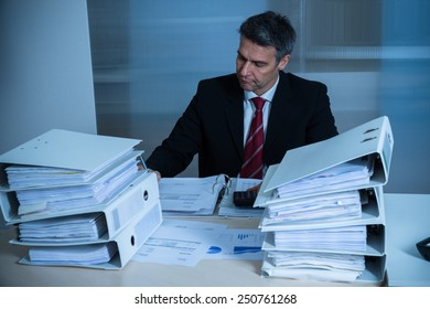 Businessman Working At Desk With Stack Of Folders