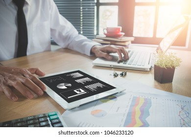 Businessman working with digital tablet and book and document on wooden desk in modern office.Toop view Business analysis and strategy concept.