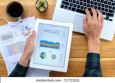 Businessman working with digital tablet and book and document on wooden desk in modern office.Top view Business analysis and strategy concept.