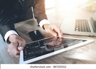businessman working with digital tablet computer and smart phone and laptop with financial business strategy layer effect on wooden desk as concept