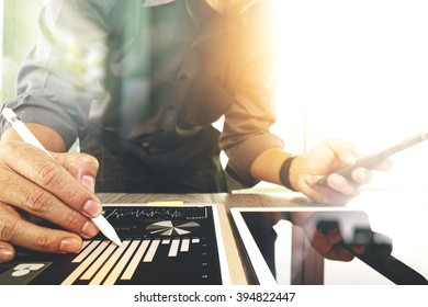 businessman working with digital tablet computer and smart phone with digital business strategy layer effect on wooden desk as concept