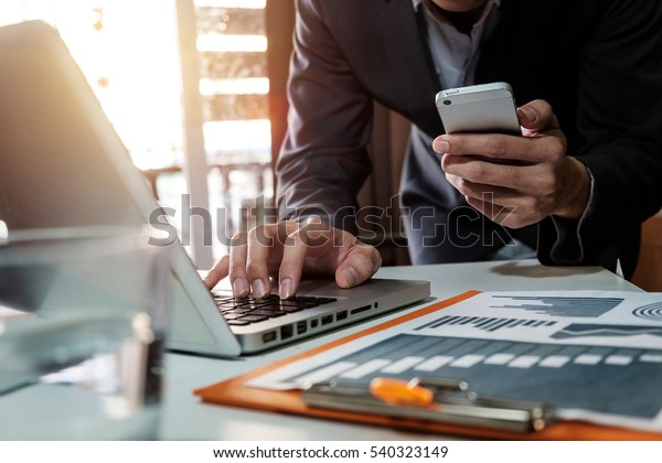 businessman working with digital tablet computer and smart phone with financial business strategy layer effect on desk in morning light