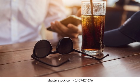 Businessman working dinner with smartphone online and sunglasses, cap fashion, cola soft drink close up on table at beach sunset his consult about project market together.