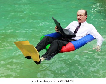 A businessman working from home dressed in business attire floating in a swimming pool on his laptop and wearing yellow flippers, and testing the water with his left hand