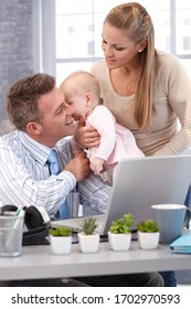 Businessman working from home father sitting at desk, working with laptop computer, wife holding baby daughter for kiss.