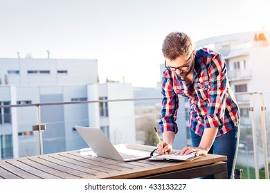Businessman working from home on laptop, standing on balcony