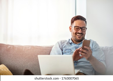 Businessman working at home using lap top. Home office. Young man sitting relaxed on sofa with laptop and smartphone. Happy young man using a mobile phone on the sofa at home