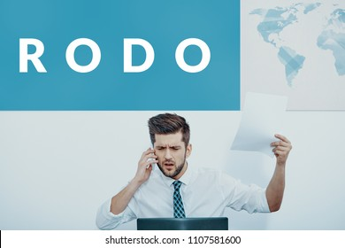Businessman working in an international company talking on the phone in front of his laptop, feeling nervous because of the new RODO regulation