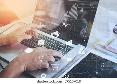 businessman working with laptop computer and digital tablet and book and document on wooden desk in modern office with virtual icons interface