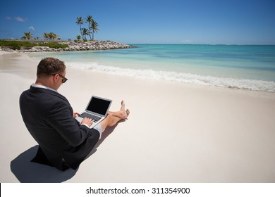 Businessman working with laptop computer on the beach