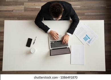 Businessman working with laptop and documents sitting at office desk, employee or company ceo using online apps software at workplace, man in suit typing on computer, top overhead view from above