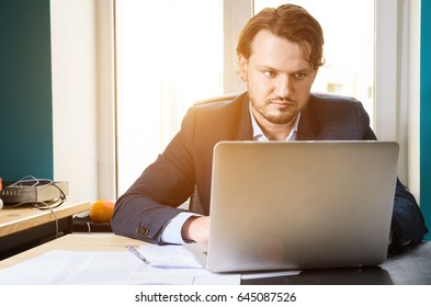 Businessman working laptop in modern loft office at sunset