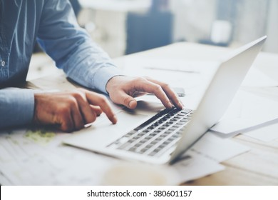 Businessman working laptop for new architectural project. Generic design notebook on the table. Blurred background, horizontal mockup.