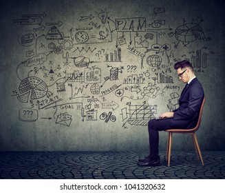 Businessman working with laptop on a business plan on the wall background full of economy drawings