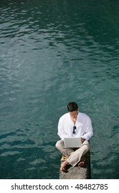 Businessman working with laptop on a pontoon