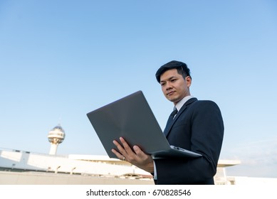 Businessman working with laptop on the roof of building in the evening,