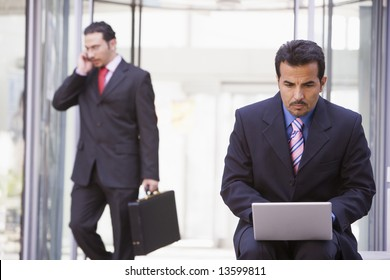 Businessman working at laptop outside office