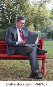 Businessman working with a laptop while sitting on a red bench in a park