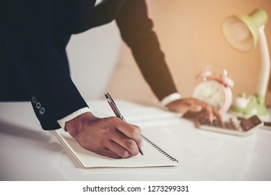 businessman working at laptop and writing in notebook in modern office