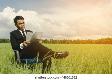 Businessman working in the midst of nature with sunlight.