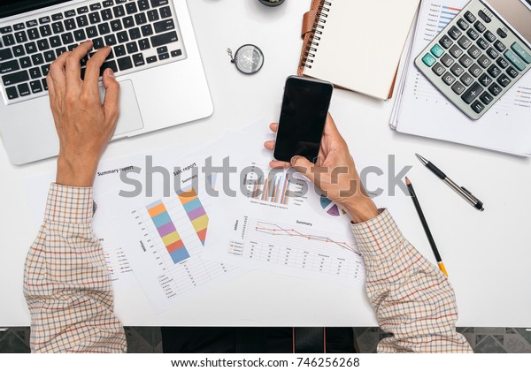 Businessman working with modern laptop computer and smart phone with financial business strategy layer effect on desk in morning light