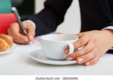 Businessman working in office with cup of coffee