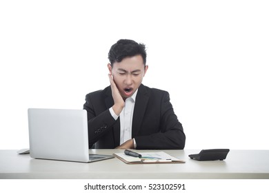 Businessman working at office desk and signing a document, computers and paperwork all around