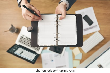 Businessman working at office desk and writing down notes on his agenda, laptop and financial report on background, top view.