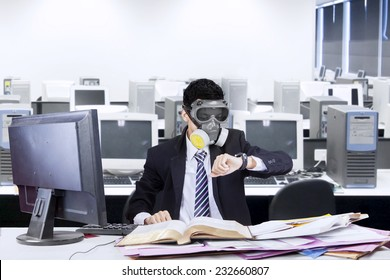 Businessman working in office with a gas mask and looking at his watch