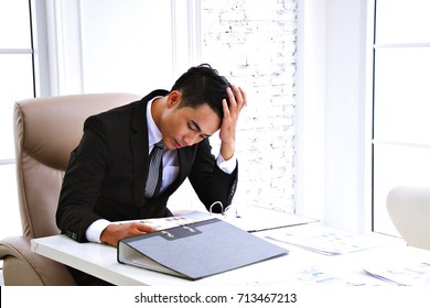 Businessman is working in the office. He is stressed.