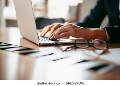 Businessman working in the office on the laptop. Man hands in business suite in conference room. Company executive working on computer. Manager preparing business presentation.