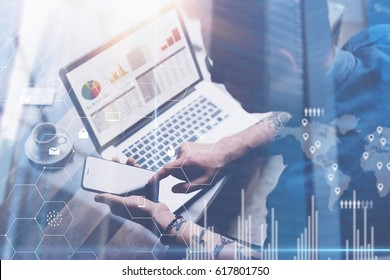 Businessman working at office on laptop.Man holding smartphone in hands.Concept of digital screen,virtual connection icon,diagram,graph interfaces on background.Double exposure