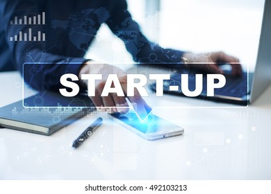 "Businessman is working in office, pressing button on virtual screen and selecting ""Start-up"". Business concept."