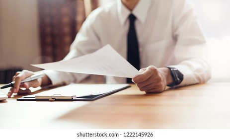 Businessman working at office with sign a document and laptop. Concept of modern business. Vintage tone.