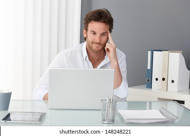 Businessman working at office, sitting at desk, looking at laptop computer screen, smiling, thinking.