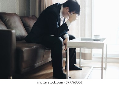 Businessman is working at the office.He is very stressed with unsuccessful work.He is sitting on brown sofa and hand held head.