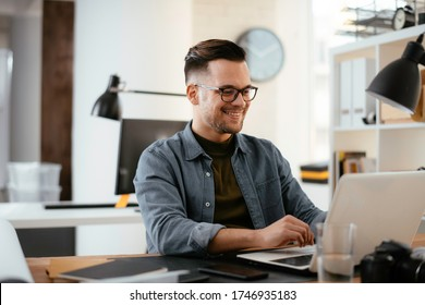 Businessman working in office. Young handsome man working on lap top.