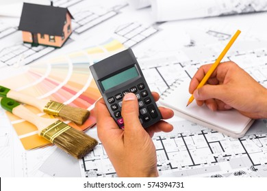 businessman working on accounts using a calculator and writing on notebook. Construction plans with Color Palette and Miniature House on blueprints; Business and Construction Industry Concept