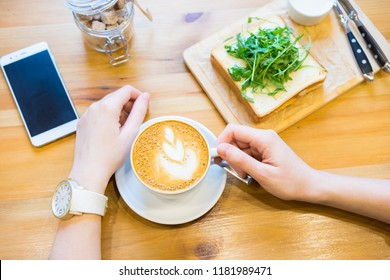 businessman working on checking business news and drinking coffee at business cafe  ;businessman drinking cappuccino and breakfast  at morning time