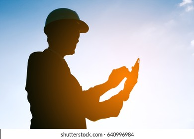 businessman working on checking equipment to use smartphone technology at solar power plant
