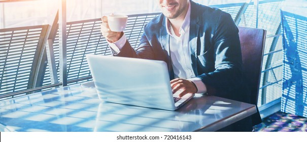 businessman working on computer, drinking coffee and smiling, abstract business banner background with place for text